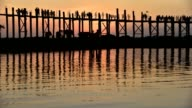 wooden bridge with pedestrians at sunset in Myanmar