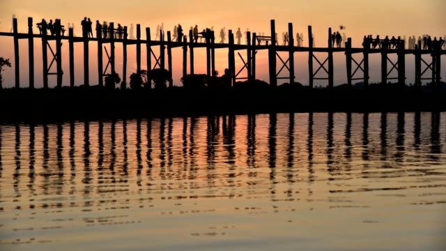 wooden bridge with pedestrians at sunset in Myanmar