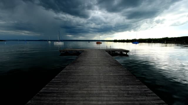 Wooden jetty on lake with a rising thunderstorm, Inning Stegen, Fuenfseenland, Upper Bavaria, Bavaria, Germany
