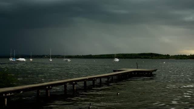 Wooden jetty on lake with thunderstorm and lightning, Inning Stegen, Fuenfseenland, Upper Bavaria, Bavaria, Germany