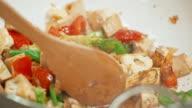 Houten lepel wordt gebruikt om het roer van groenten in de koekenpan