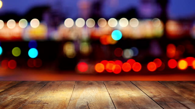 Wooden table in front of abstract background of city lights