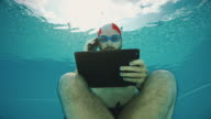 Workaholic man underwater with mobile and tablet
