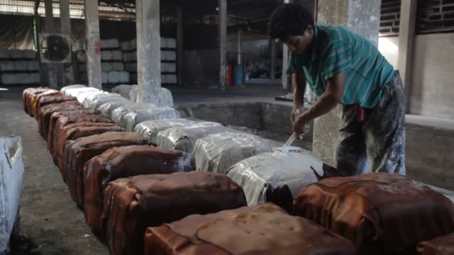A worker applies a calcium carbonate solution used as a resistant and to prevent molding to stacks of smoked rubber sheets in a warehouse as well as...
