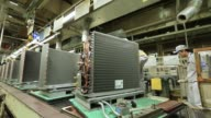 A worker assembles coil condensers for Daikin Industries Ltd air conditioners on the production line of the company's Shiga plant in Kusatsu Shiga...