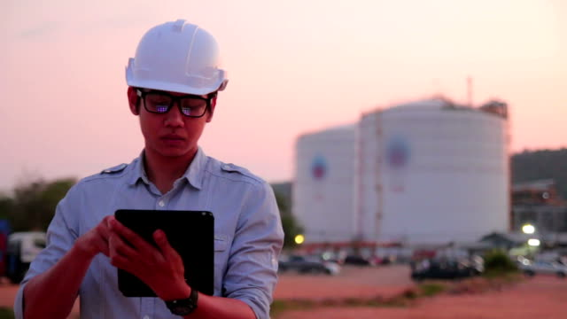 Worker at industrial plant working on a tablet.