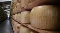 A worker carries a whole Parmigiano Reggiano cheese and places onto a storage rack ahead of inspection at Coduro cheesemakers in Fidenza Italy on...