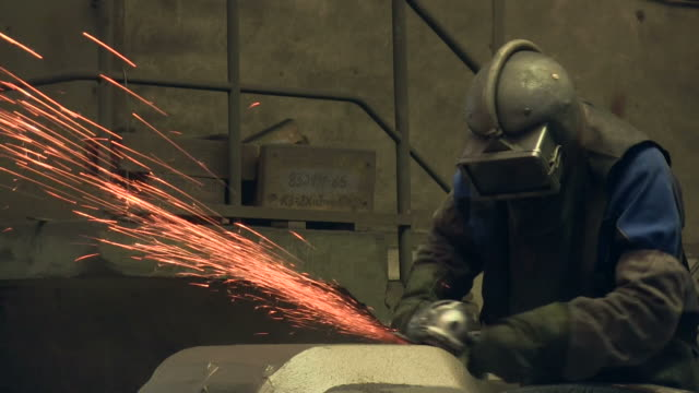 MS Worker cleaning work pieces at foundry / Junckerath, North Rhine-Westphalia, Germany