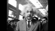 / worker completes huge telescope mount as crowd watches / scientists Albert Einstein and Robert Millikan watch / Einstein inspects scale model of...
