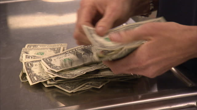MS ZI Worker counting dollar bills by hand / Kansas City, Kansas, United States