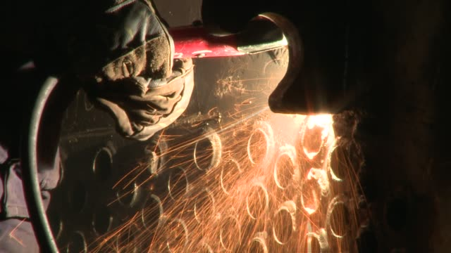 A worker creates sparks while using a grinder. Available in HD.