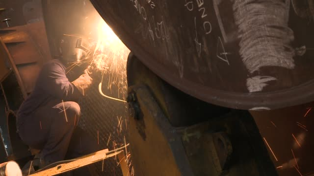 A worker creates sparks while using a welder. Available in HD.