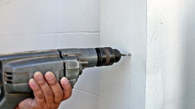 Worker drilling into wall