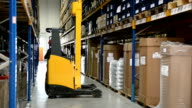 Worker drives forklift in warehouse
