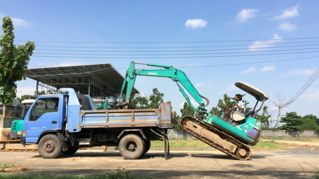 worker driving pushcart down from truck