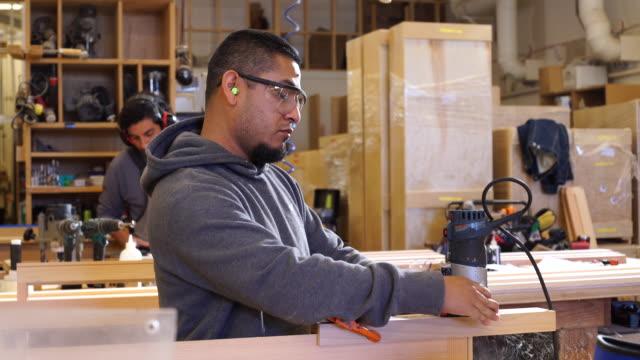 Worker finishes custom window frames using hand-held power sander