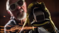 Worker grinding a metal construction - Rack Focus
