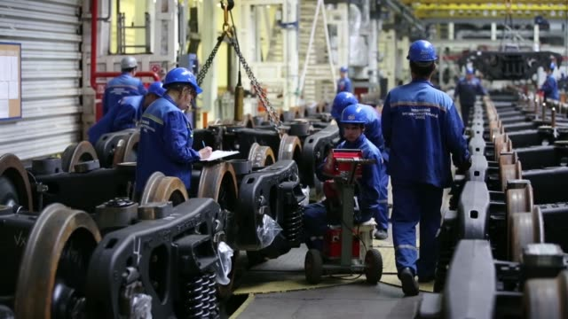 A worker guides a bogie trolley for rolling stock during wagon manufacture at the Tikhvin Freight Car Building Plant in Tikhvin Russia on Friday Oct...