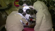 A worker in protective clothing turns the handle on a refurbishing tool attached to a tube channel as a coworker watches.