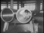 Worker inspects torpedo / man crawls through tube / workers insert propeller into torpedo test blades / testing barge in Potomac River / soldiers...