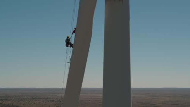 Worker lowering down a wind turbine blade