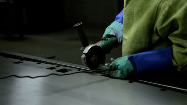 Arbeitnehmer macht Einschnitte auf dem Blech durch die Angule-Schleifmaschine.