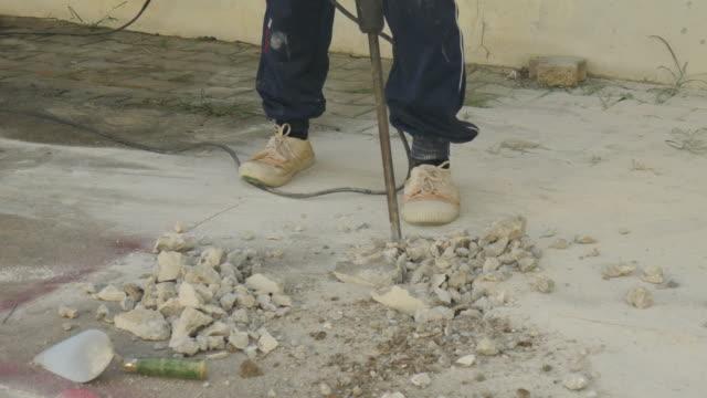 Worker man drilling cement concrete floor.
