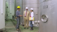 WS Worker, manager and lab technician talking near storage tanks / Sanlucar de Barrameda, Andalusia, Spain