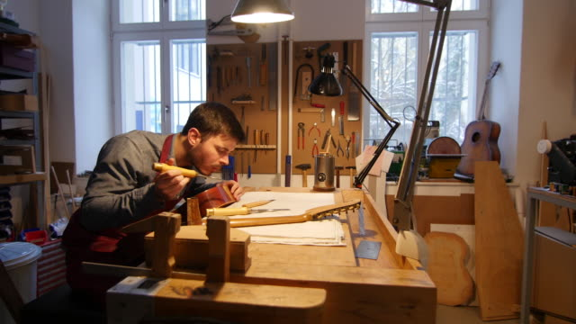 Worker manufacturing guitar at table