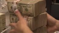 CU ZO Worker moving stacks of 50 dollar bills on table / Kansas City, Kansas, United States