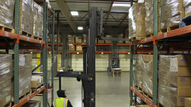 A worker operating a forklift in a warehouse