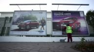 A worker pastes new posters of the Ford Edge left and Mustang automobiles manufactured by Ford Motor Co outside the Porte de Versailles metro station...