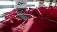 A worker prepares jackets for embroidering machine Close view of brand embroidered by machine Workers use sewing machines at a garment workshop Close...