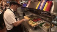 WGN Worker Prepares Line of ChicagoStyle Hot Dogs at Portillo's restaurant in Chicago on National Hot Dog Day on July 19 2017