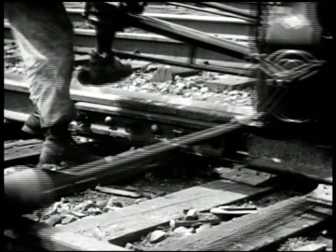 Worker putting in bolts on tracks CU Man operating bolt tightening machine CU Man using spike driver on spikes nails on wooden planks in track Labor...