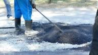 worker repair road asphalt paver applying asphalt on the road