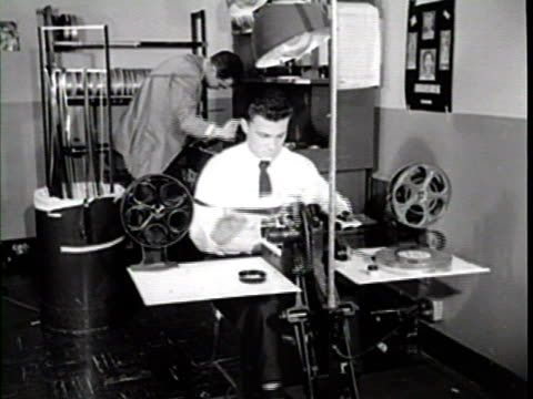 worker running 35mm film film through film counter at rewind table / closeup of film counter / another worker splicing 35 mm sound film at inspection...