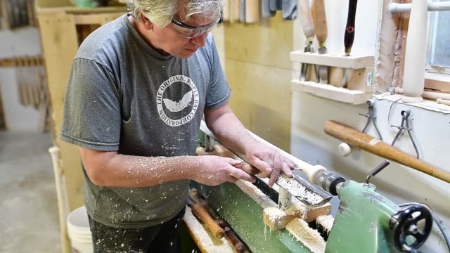 A worker sands and shapes baseball bats in slow motion footage of Sam Bat baseball bat manufacturer in Ottawa Canada on October 24 2017 Photographer...