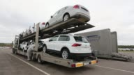 A worker secures a new VW automobile to a Group Cat transporter before shipping at the Volkswagen Group Rus OOO plant in Kaluga Russia on Tuesday...