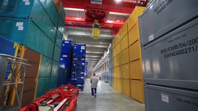 A worker secures a winch to a container of radioactive waste in a temporary storage facility during decommissioning operations at Lubmin nuclear...