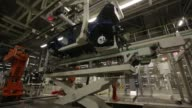 A worker sits on an elevated seat to fit parts to a VW Tiguan automobile on the production line at the Volkswagen Group Rus OOO plant in Kaluga...
