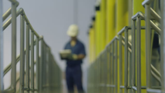 LS RF worker standing on gangway and writing on clipboard; RF from de-focussed to in-focus on worker, RED R3D 4K