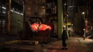A worker stands beside a large steel component in the forge area of Sheffield Forgemasters International Ltd in Sheffield UK on Monday July 22 An...