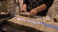 CU Worker straightening out stacks of one dollar bills before placing on conveyor belt / Kansas City, Kansas, United States