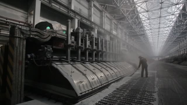 A worker sweeps the floor beside electrolysis baths in the electrolysis shop at the Sayanogorsk aluminium smelter operated by United Co Rusal in...