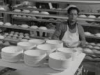 A worker takes saucers from a rotating rack and stacks them at a pottery workshop