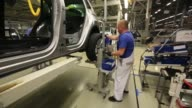A worker tightens the wheel nuts of a VW Tiguan automobile on the production line at the Volkswagen Group Rus OOO plant in Kaluga Russia on Tuesday...