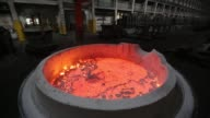 A worker uncovers a cauldron of liquid electrolyte inside the electrolysis shop at the Krasnoyarsk aluminum smelter operated by United Co Rusal in...