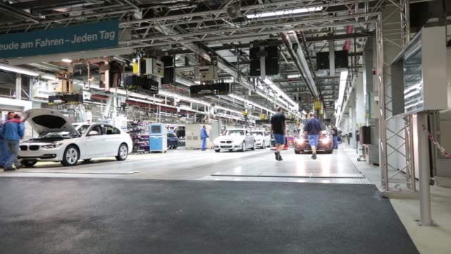 A worker uses a platform to test the tracking on the wheels of a BMW 3 series automobile as it moves along the production line at the Bayerische...