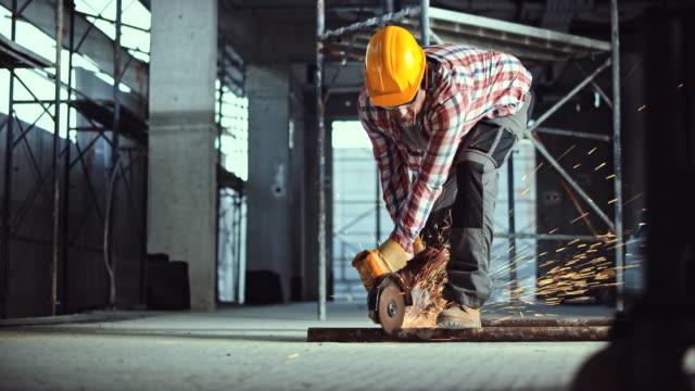 Arbetstagare med en vinkelslip för att skära igenom ett metallrör på golvet vid byggplatsen